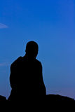 Silhouette of monk meditating Stock Photo