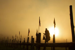 Silhouette Monk walking sunset. Silhouette of Thai rural Monk walking on the bamboo bridge with sunrise background. Place name Sutongpe Bridge. the longest Royalty Free Stock Photography