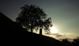 Silhouette of a monument next to a tree. In the sunset with a cloudy sky Royalty Free Stock Image