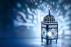 Silhouette of Moroccan lantern with burning glowing candle. Decorative shadows. Festive greeting card, invitation for. Muslim holy month Ramadan Kareem, blue royalty free stock photos