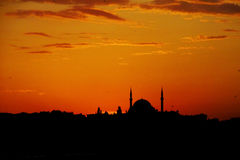 Silhouette of a mosque minaret at sunset Stock Photos