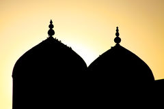 Silhouette of a mosque in the sunset sky. Silhouette of a mosque in Khudjand, Tajikistan, in the yellow sunset sky Stock Image