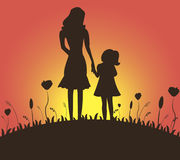 Happy addition to the family. Silhouette of mother and adoptive daughter against the background of sunrise Royalty Free Stock Photos