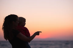 Silhouette of mother with baby in sunset on beach Stock Photos