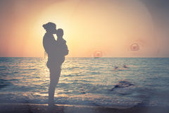 Silhouette of mother and child on the beach, and a child's face Stock Photos
