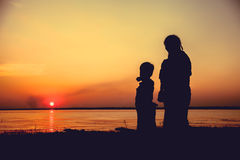 Silhouette of mother and child enjoying the view at riverside. Royalty Free Stock Photography