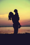 Silhouette of mother and child enjoying the view at riverside. C Stock Images