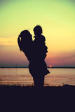 Silhouette of mother and child enjoying the view at riverside. C Royalty Free Stock Photo