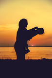 Silhouette of mother and child enjoying the view at riverside. Royalty Free Stock Photo