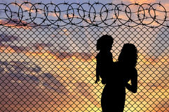 Silhouette of mother and child refugees Stock Image
