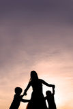 Silhouette of Mother and Children Dancing at Sunset. Silhouette of a mother and her two young children holding hands and dancing around outside, isolated against royalty free stock images