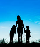 Silhouette mother and children holding hands at sunset Royalty Free Stock Photo