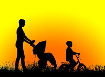 Silhouette mother with children walking at sunset Stock Image