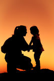 Silhouette of mother and daughter clasping hand together at suns Royalty Free Stock Image