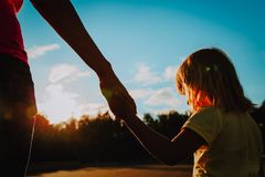 Silhouette of mother and daughter holding hands at sunset. Nature Stock Photos