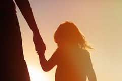 Silhouette of mother and daughter holding hands at sunset stock photo