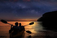 Silhouette mother and daughter kayaking in the ocean with million stars galaxy. And sunrise sky early morning stock image