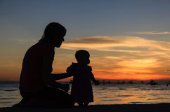 Silhouette of mother and daughter on sunset beach Royalty Free Stock Photography