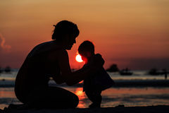 Silhouette of mother and daughter on sunset beach Stock Photo