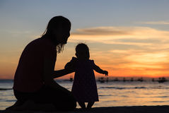 Silhouette of mother and daughter on sunset beach Stock Images