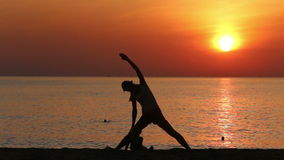 Silhouette of mother doing exercises at sunrise above sea. Silhouette of mother doing exercises by bending left and right on beach against sunrise above sea stock footage