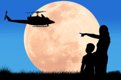 Silhouette  mother hand point to helicopter at the full moon nig Royalty Free Stock Photos