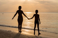 Silhouette mother with her son on the beach during sunset Royalty Free Stock Photography