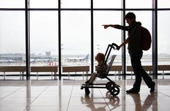 Silhouette of mother with her toddler son in stroller against the window at the airport. Mom points the direction with her finger royalty free stock photos