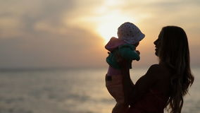 Silhouette of mother holding toddler on hands at. Silhouette of mother holding toddler on her hands at sunset near the sea in slow motion