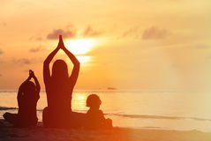 Silhouette of mother and kids doing yoga at sunset. Sea Stock Image