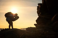 Silhouette mother kiss child at sunset Stock Photos