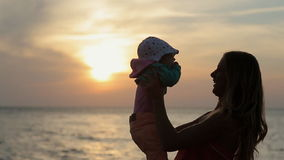 Silhouette of mother kissing baby at sunset near. Silhouette of young mother kissing baby at sunset near the sea in slow motion stock footage