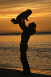 Silhouette of mother lifting her child at sunset Royalty Free Stock Images