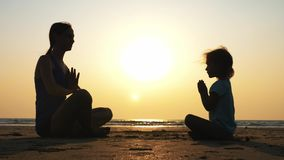 Silhouette of mother with little daughter meditating together at sunset stock footage