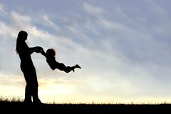 Silhouette of mother Playing with Child Outside at Sunset. A silhouette of a playful young mother spinning and dancing with her little child outside at sunset on Stock Photography