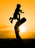 Silhouette of mother playing with her son Royalty Free Stock Photo