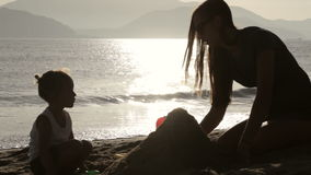 Silhouette of mother and small daughter building sand castles on the beach stock video footage
