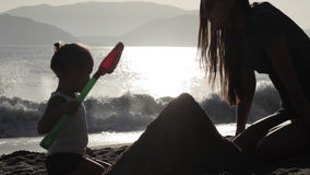 Silhouette of mother and small daughter building sand castles on the beach stock footage