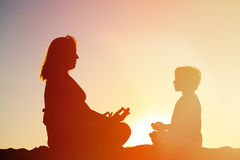 Silhouette of mother and son doing yoga on beach. Silhouette of mother and son doing yoga on sunset beach stock images