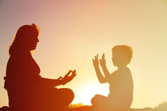 Silhouette of mother and son doing yoga on beach. Silhouette of mother and son doing yoga on sunset beach stock image