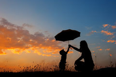 Silhouette of a mother and son holding umbrella and playing outd Stock Photos
