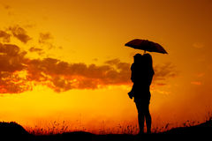 Silhouette of a mother and son holding umbrella and playing outd. A mother and son holding umbrella and playing outdoors at sunset silhouette stock image