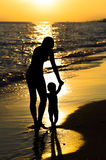 Silhouette mother and son. Silhouette mother leads the child's hands in the sunset by the sunset Stock Images