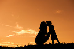Silhouette of a mother and son playing outdoors at sunset with copy space Royalty Free Stock Images