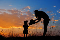 Silhouette of a mother and son playing outdoors at sunset Royalty Free Stock Photography