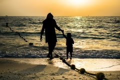 Silhouette of a mother and son walking a the beach. Mothers day Stock Photo