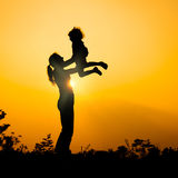 Silhouette of a mother and son who play outdoors at sunset backg Royalty Free Stock Photos