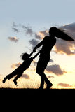 Silhouette of Mother Spinning and Dancing with Child at Sunset Royalty Free Stock Images