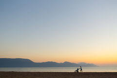 Silhouette of mother with stroller enjoying motherhood at sunset Stock Photo