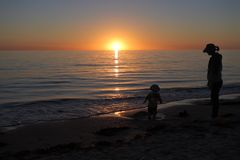 Silhouette of mother and toddler looking at sunset. Over Henley Beach in Adelaide South Australia stock image